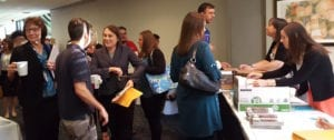 Several attendees of 2016 Annual Meeting gather in hallway and engage in conversation while waiting at registration table