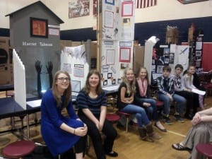 Six students sit in a line in front of three exhibit boards in a school cafeteria.
