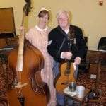 Steve and Lisa Ball in Civil-War era dress standing with musical instruments